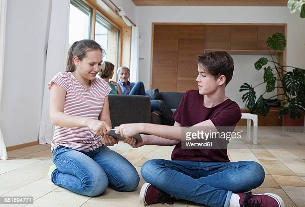 Teenage siblings fighting over tablet in living room with parents in background