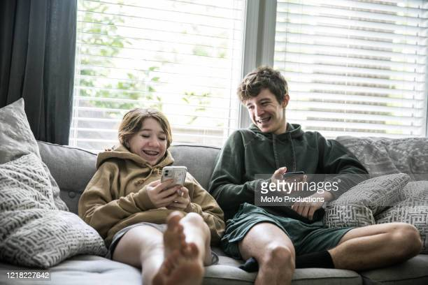 teenage siblings looking at smartphones and laughing - 外出禁止令 ストックフォトと画像