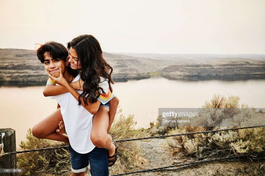 Teenage sister squeezing bothers face while riding piggy back : Stock Photo