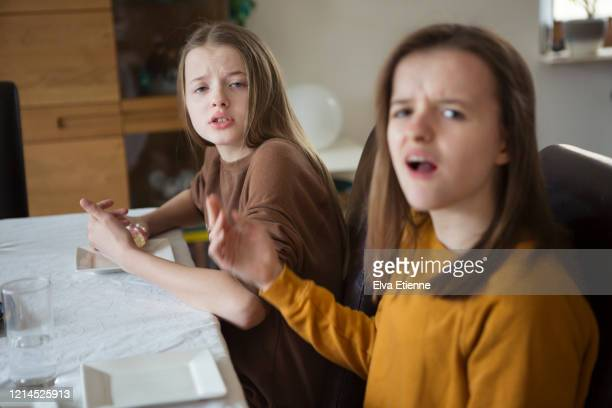 teenage sisters expressing annoyance during an argument at a dining table - klagen stockfoto's en -beelden