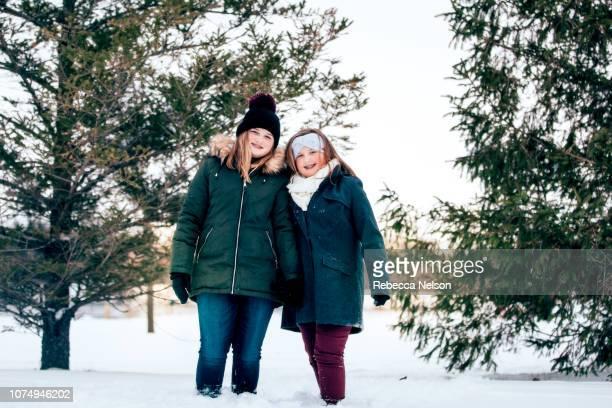 teenage sisters hiking in snow