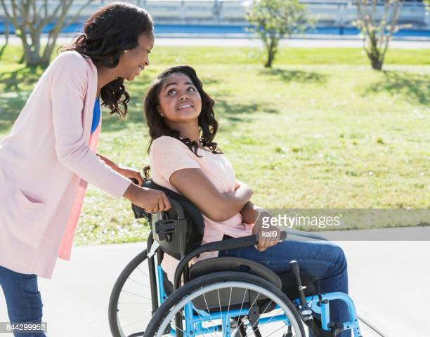 teenage sisters, one in a wheelchair - spinal cord injury stock photos and pictures