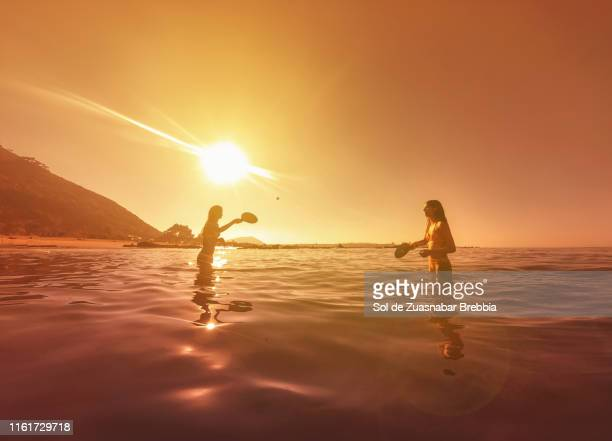 teenage sisters playing tennis in the sea on a wonderful sunset - hot spanish women stock pictures, royalty-free photos & images