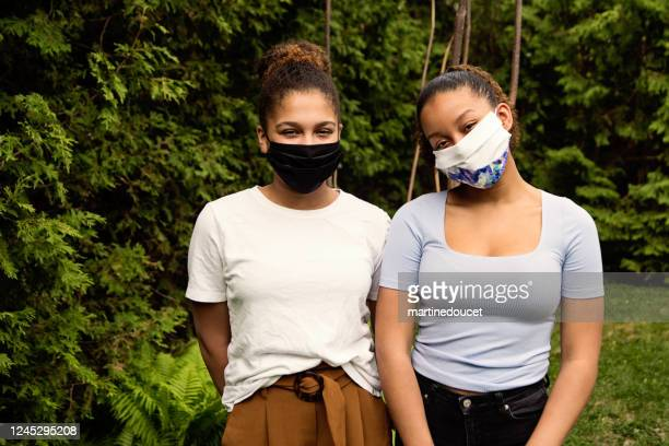 """teenage sisters smiling behing stylish protective mask. - """"martine doucet"""" or martinedoucet stock pictures, royalty-free photos & images"""