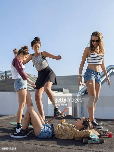teenage skateboarders having fun on rooftop - girls with short skirts - fotografias e filmes do acervo