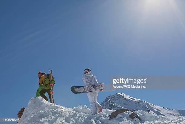 Teenage snowboarder climbs ridge crest to friends
