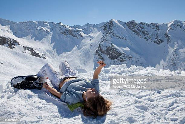 Teenage snowboarder relaxes on ridge, with mp3