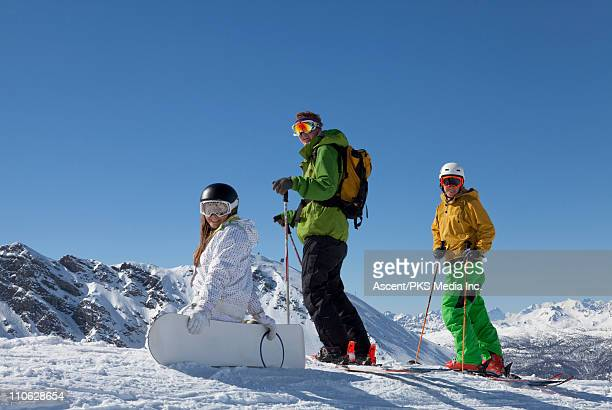Teenage snowboarders/skiers pause on ridge crest