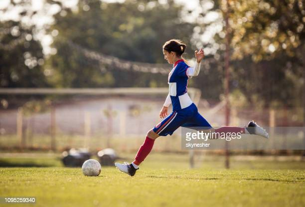 teenage soccer player about to kick the ball during the match. - women's football stock pictures, royalty-free photos & images