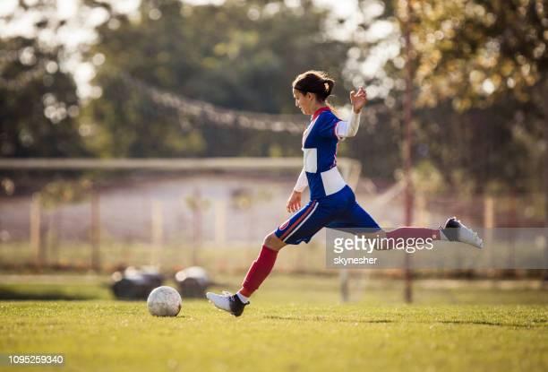joueur de soccer adolescente sur le point de frapper le ballon pendant le match. - football féminin photos et images de collection