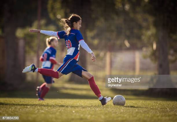 teenage soccer player in action on a playing field. - striker stock pictures, royalty-free photos & images