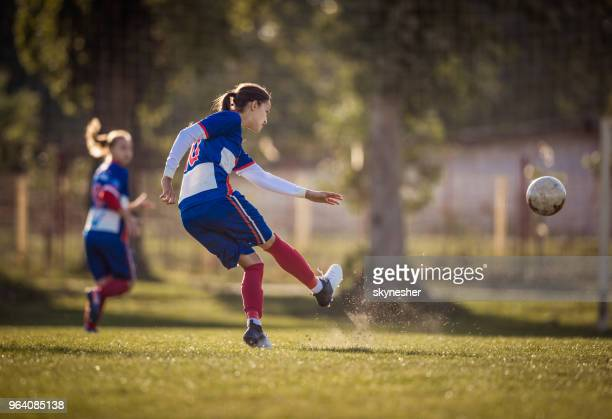 teenage soccer player in action on a playing field. - shooting at goal stock pictures, royalty-free photos & images