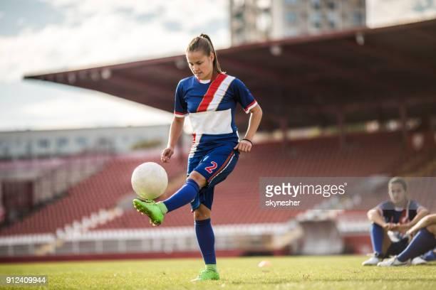 joueur de soccer teenage botter le ballon sur un entraînement au stade du sportif. - football féminin photos et images de collection