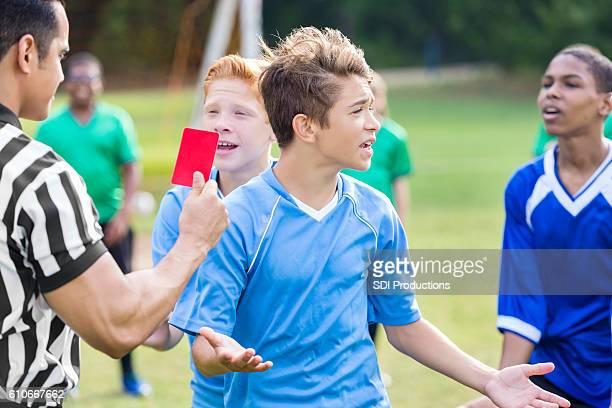 el jugador de fútbol adolescente se opone a la llamada de penalti del árbitro - oficial deportivo fotografías e imágenes de stock