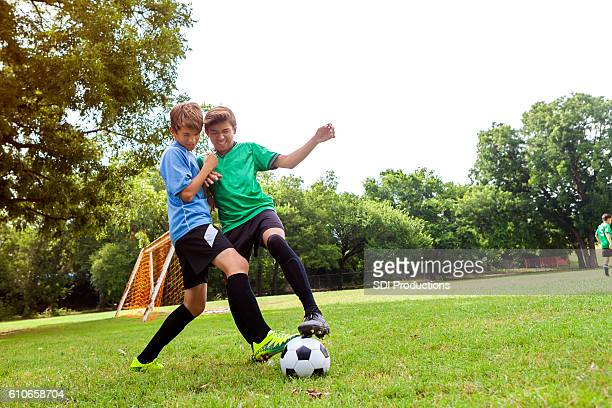 Teenage soccer player oppose one another on the field
