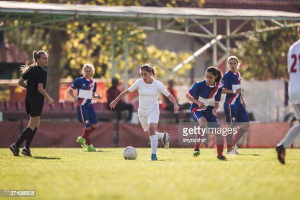 teenage soccer player running with ball and tackling her opponents. - soccer competition stock pictures, royalty-free photos & images