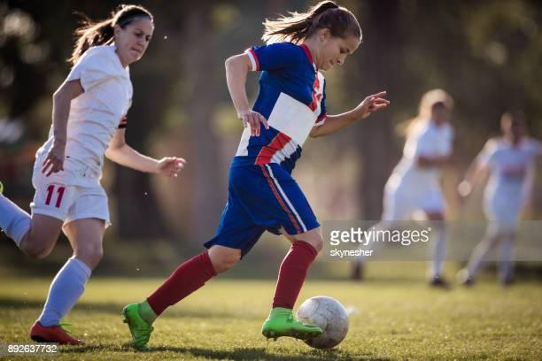 joueur de football chez les adolescentes en cours d'exécution avec la balle alors qu'il tentait d'éviter son adversaire sur un match. - football féminin photos et images de collection