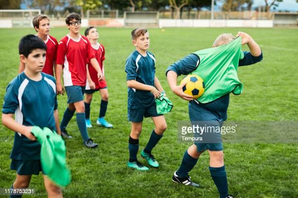 teenage soccer-spelers verlaten het veld na een trainingssessie. - voetbalteam stockfoto's en -beelden