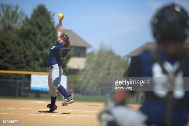 Teenage softball player throwing a pitch.