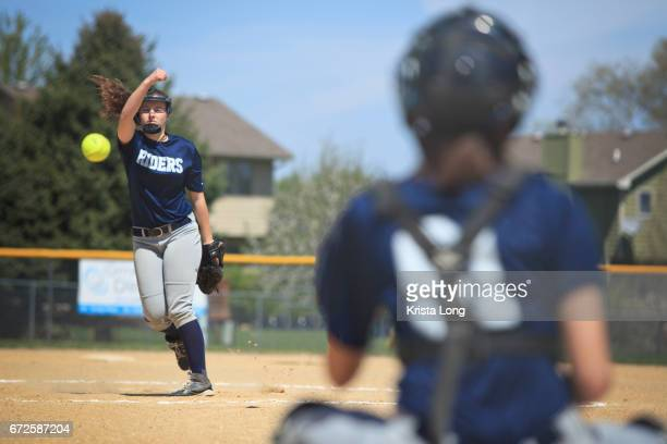 teenage softball player throwing a pitch. - softball stock pictures, royalty-free photos & images