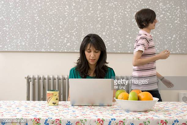 Teenage son (13-15) walking by mother using laptop computer at table