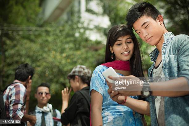 Teenage student Friends of different ethnicity sharing smartphone near campus.