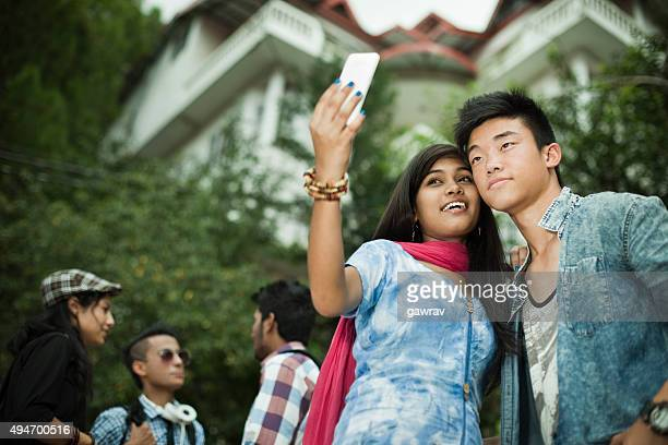 teenage student friends of different ethnicity taking selfie near campus. - indian college girls stock photos and pictures