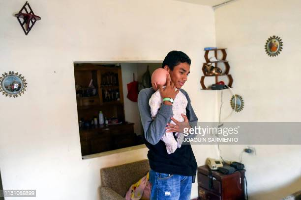 Teenage student Miguel Angel Suarez takes care of a baby robot at his home in Caldas Antioquia's department Colombia on May 19 2019 Schoolchildren in...