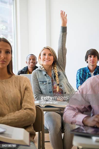Teenage student raising hand in classroom