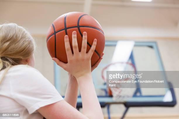 Teenage student shooting basketball