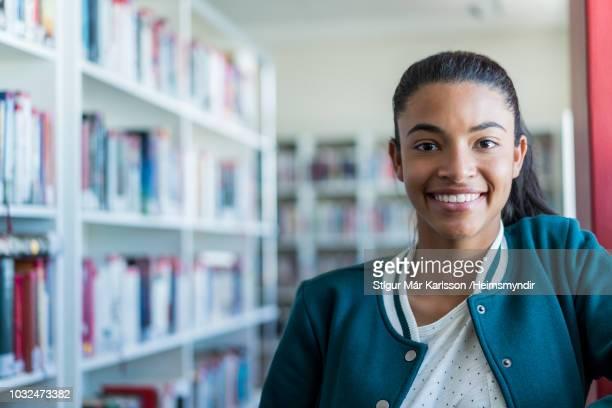 Tiener student glimlachend in de schoolbibliotheek