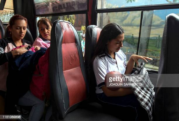 Teenage student Susan Ortegon carries a baby robot on her way home after school in Caldas Antioquia's department Colombia on May 17 2019...