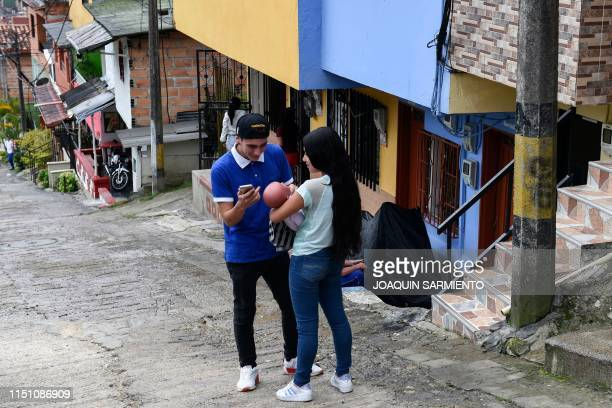 Teenage student Susan Ortegon speaks with a neighbour while caring a baby robot in Caldas Antioquia's department Colombia on May 19 2019...