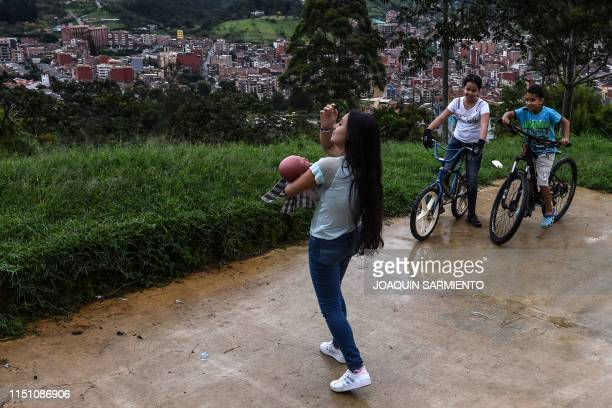 Teenage student Susan Ortegon takes care of a baby robot as she walks around her neighborhood in Caldas Antioquia's department Colombia on May 19...