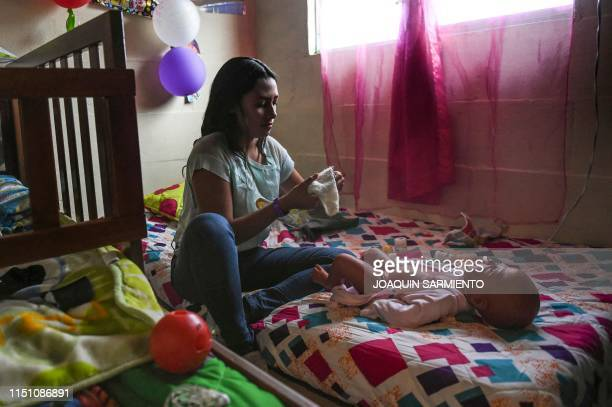 TOPSHOT Teenage student Susan Ortegon takes care of a baby robot at her home in Caldas Antioquia's department Colombia on May 19 2019 Schoolchildren...
