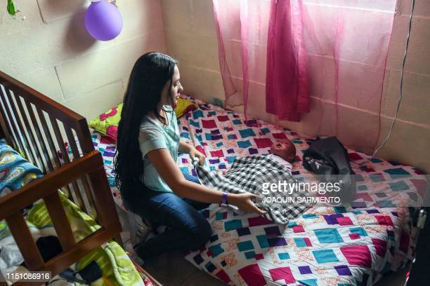 Teenage student Susan Ortegon takes care of a baby robot at her home in Caldas Antioquia's department Colombia on May 19 2019 Schoolchildren in...