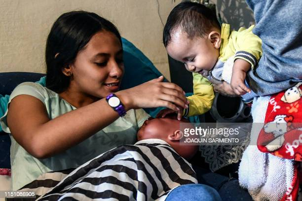 Teenage student Susan Ortegon takes care of a baby robot next to her baby cousin at her home in Caldas Antioquia's department Colombia on May 19 2019...