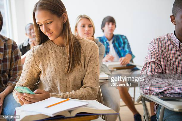 Teenage student using cell phone in classroom