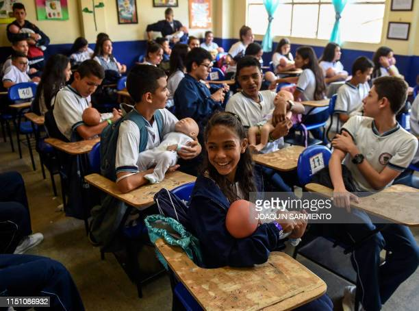 Teenage students carry baby robots during a sex education class at a school in Caldas Antioquia's department Colombia on May 17 2019 Schoolchildren...