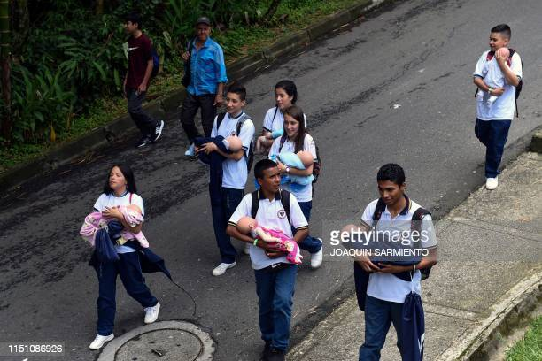 Teenage students carry baby robots on their way home after school in Caldas Antioquia«s department Colombia on May 17 2019 Schoolchildren in Caldas...