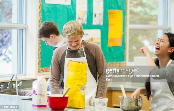 Teenage students laughing in cookery class