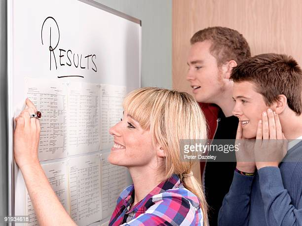 teenage students looking for exam results on board - three people stock pictures, royalty-free photos & images
