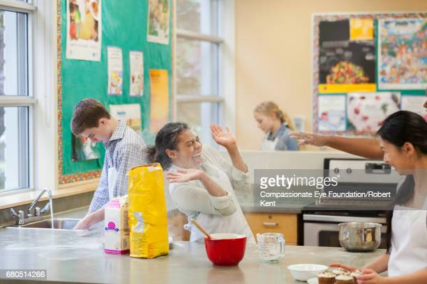 Teenage students messing about with flour in cookery class