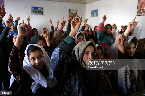 Teenage students raise their hands during math class December 27 2001 at Ariana High School in Kabul Afghanistan Some schools have started winter...