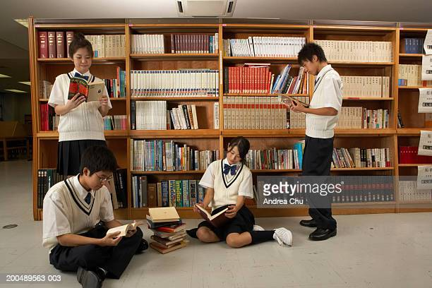 Teenage students (12-16) reading books in library