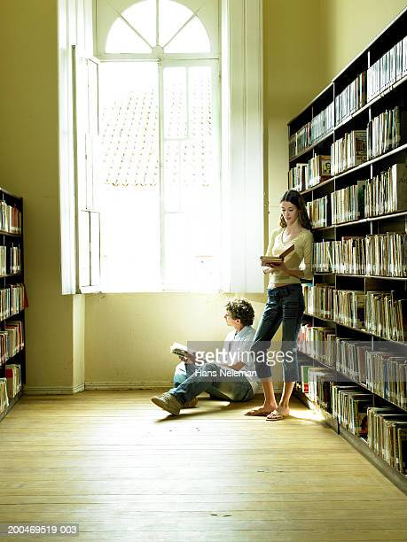 Teenage students (15-17) reading by library shelves