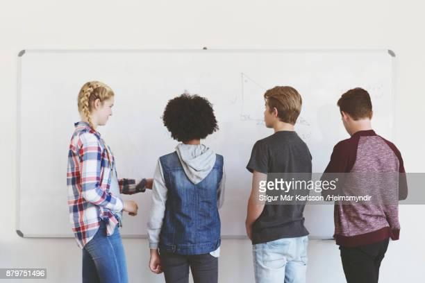 ホワイト ボードの前に立っている 10 代学生