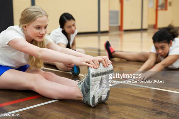 teenage students stretching in gym - physical education stock pictures, royalty-free photos & images