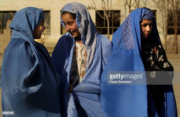 Teenage students wearing burqas chat after classes December 27 2001 at the Ariana High School in Kabul Afghanistan Some schools have started winter...