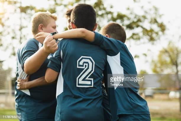 une équipe d'adolescents s'embrasse et célèbre marquer un but. - par équipe photos et images de collection